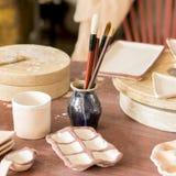 Een reeks borstels en toebehoren voor het schilderen van keramiek Creatieve workshop stock foto's