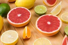 Een reeks gesneden citrusvruchten ligt samen op een houten raad stock afbeeldingen