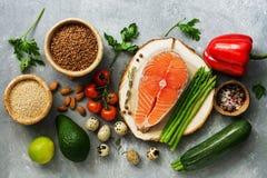 Een reeks gezond evenwichtig super voedsel, verse zalm, groenten, ei, graangewassen en noten op een grijze achtergrond De hoogste stock fotografie