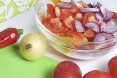 Een reeks groenten voor salade ligt dichtbij de scherpe raad Mes voor knipsel en een container voor salade Stock Fotografie