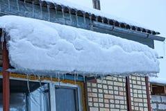 Een reeks ijskegels op het dak van de portiek onder de sneeuw door de bakstenen muur met een venster stock foto