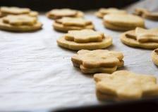 Een reeks Kerstmiskoekjes en koekjes op bakseldocument dat worden gebakken royalty-vrije stock afbeeldingen