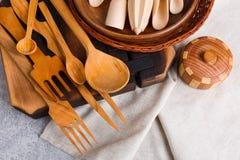 Een reeks keukenapparaten, de lepels, de lepels en de vorken, de raad en de platen worden gemaakt van hout Royalty-vrije Stock Afbeeldingen