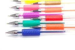 Een reeks kleurde pennen op een witte achtergrond stock foto