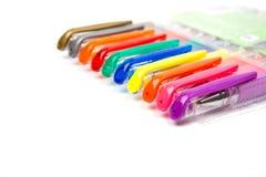 Een reeks kleurde pennen op een witte achtergrond stock foto's