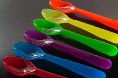Een reeks kleurrijke plastic lepels Stock Foto's