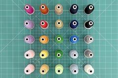 Een reeks kleurrijke spoelen van draad op groene scherpe mat royalty-vrije stock foto