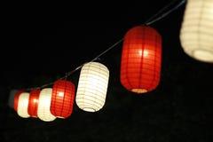 Een reeks lantaarns met achtergronddark stock afbeeldingen