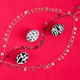 Een reeks paaseieren als zebra, een koe, een sneeuwluipaard op een rode achtergrond met gouden, zilveren kettingen en sterren wor stock afbeelding