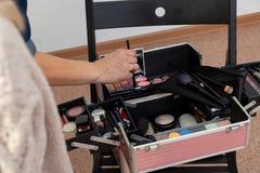 Een reeks professionele schoonheidsmiddelen in doos open dichte omhooggaand met inhoud Het meisje van de make-upkunstenaar aan he stock foto