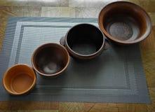 Een reeks schotels van bruine klei op de lijst, aangaande het tafelkleed stock afbeelding