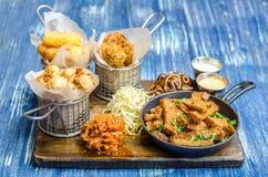 Een reeks snacks voor bier Kippenstokken in beslag, kaas, varkensvleesoren, toosts, sausen en kool op een houten raad royalty-vrije stock afbeeldingen