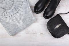 Een reeks van de modieuze kleding van de wintervrouwen ` s Wolsweater, schoenen en handtas op witte houten achtergrond Royalty-vrije Stock Foto