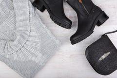 Een reeks van de modieuze kleding van de wintervrouwen ` s Wolsweater, schoenen en handtas op witte houten achtergrond Stock Afbeeldingen