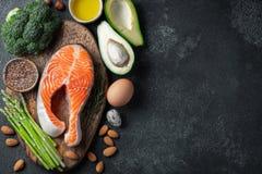 Een reeks van gezond voedsel voor keto dieet op een donkere achtergrond Vers ruw zalmlapje vlees met lijnzaad, broccoli, avocado, royalty-vrije stock fotografie