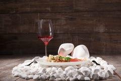 Een reeks van restaurantdelicatesse op een houten achtergrond Glas rode wijn en smakelijk vlees en kaas op witte rotsen Stock Foto's