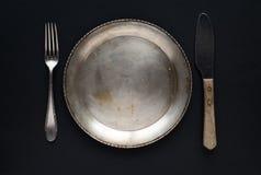 Een reeks van uitstekend vaatwerk: plaat, gekruiste vorken en lepels op een witte achtergrond Antiek Tafelzilver Retro stijl stock afbeelding