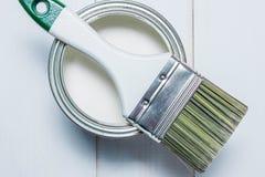 Een reeks van verfborstels en een kruik met witte verf op een geweven houten lijst geschilderd wit Royalty-vrije Stock Foto