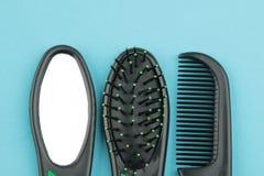 Een reeks van verschillende haarborstels en een spiegel in één stijl op een heldere blauwe achtergrond Mening van hierboven stock foto