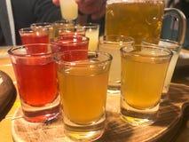 Een reeks veel heerlijke geeloranje rode glazen, schoten met sterke alcohol, wodka, brandewijn, brandewijn, bier op houten tribun stock foto's