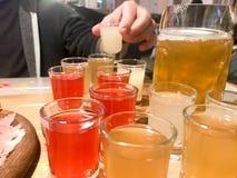 Een reeks veel heerlijke geeloranje rode glazen, schoten met sterke alcohol, wodka, brandewijn, brandewijn, bier op houten stock foto