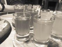 Een reeks veel heerlijke zwart-witte glazen, schoten met sterke alcohol, wodka, het vullen, brandewijn op houten tribunes op een  stock fotografie