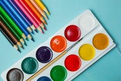 Een reeks voor creativiteit en tekening: waterverf en multicolored potloden op een blauwe achtergrond Hoogste mening stock fotografie