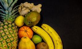 Een reeks vruchten, fruit is op de linkerzijde en een beschikbare ruimte op de juiste, zwarte achtergrond, ananassinaasappel stock fotografie