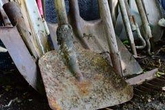 Een reeks vuile oude tuinhulpmiddelen in de grond na het seizoengebonden werk, schoppen, bijlen en harken Stock Fotografie