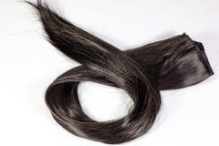 Een reeks zwarte haaruitbreidingen van roodachtig donkerbruin krullend haar op een lijst van de schoonheidswinkel stock foto's