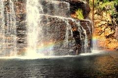 Een regenboog bij een waterval Stock Afbeelding