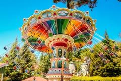 Een regenboog kleurde schommelingscarrousel bij een pretpark Royalty-vrije Stock Foto's