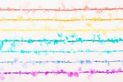 Een regenboog met dunne gekleurde pennen wordt getrokken spreidt in het water dat uit stock afbeelding