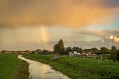 Een regenboog wordt weerspiegeld in het water van een kanaal dichtbij Gouda, Nederland stock foto's