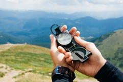 Een reiziger in de bergen met een kompas stock afbeelding