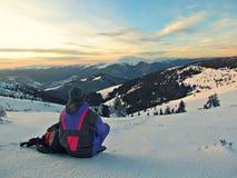 Een reiziger die op de de winterbergen kijken Stock Foto's