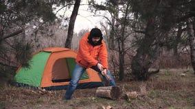 Een reiziger in een heldere jasje en de winterhoed snijdt brandhout voor het maken van een brand op de achtergrond van een toeris stock footage