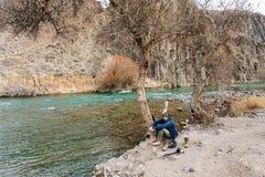 Een reiziger met een camera die op de bank van een bergstroom rusten Hij droogt zijn kleren en schoenen Stock Fotografie