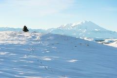 Een reiziger met een grote rugzak op zijn schouders zit op een snow-capped heuvel tegen de blauwe hemel en de slaap Stock Foto's