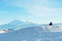 Een reiziger met een grote rugzak op zijn schouders zit op een snow-capped heuvel tegen de blauwe hemel en de slaap Royalty-vrije Stock Afbeeldingen