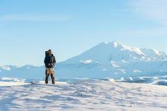 Een reiziger met een grote rugzak op zijn schouderstribune op een snow-capped heuvel tegen de blauwe hemel en de slaap Royalty-vrije Stock Foto