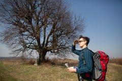 Een reiziger met een rugzak die, die de kaart bekijken en in het platteland lopen Boom op de achtergrond stock afbeeldingen