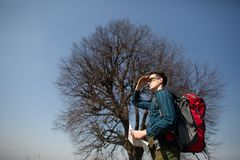 Een reiziger met een rugzak die, die de kaart bekijken en in het platteland lopen Boom op de achtergrond royalty-vrije stock foto's
