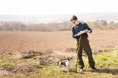 Een reiziger met een rugzak en zijn hond die, die de kaart bekijken en in het platteland lopen stock fotografie