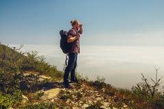 Een reizigersmens onderzoekt de afstand die zich bovenop een berg bevinden Reislevensstijl Royalty-vrije Stock Fotografie