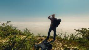 Een reizigersmens onderzoekt de afstand die zich bovenop een berg bevinden Reislevensstijl Stock Foto's