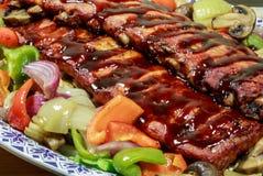 Een rek van ribben met van het barbecuesaus en braadstuk groenten worden gekookt die royalty-vrije stock foto