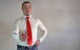 Een respectabele mens in een bedrijfsstijl in een wit overhemd met een rode band en grote handen op een witte achtergrond stock foto's