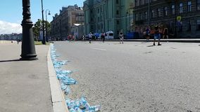 Een reusachtig aantal verworpen waterflessen aan de kant van de weg en de lopende marathondeelnemers op de achtergrond Het huisvu stock footage