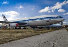 Een reusachtig blauw en wit vliegtuig bevindt zich op de oude weg van de barst op een achtergrond van blauwe hemel met wolken stock foto's